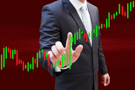 nyse: Businessman hand touching Candlestick Chart, investment concept