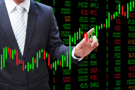 Businessman hand touching Candlestick Chart, investment concept