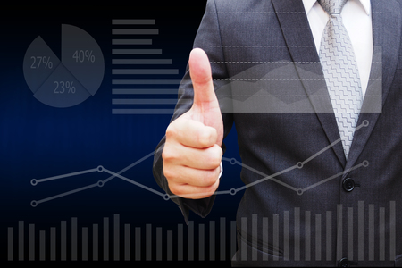 pay wall: Businessman hand thumbs with the virtual panel of pir chart and other chart , business concept