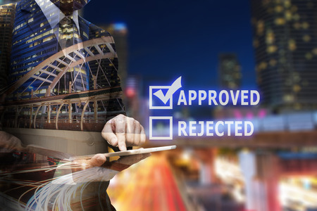 Double exposure businessman hand using digital tablet with checked check box of approved or rejected Stock Photo