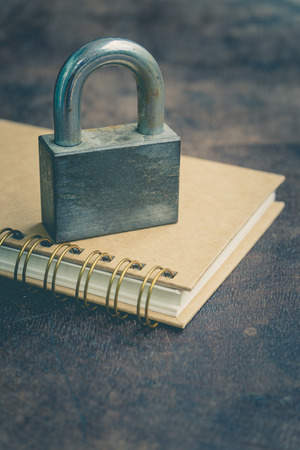 Notebook on wooden table and old padlock Lizenzfreie Bilder