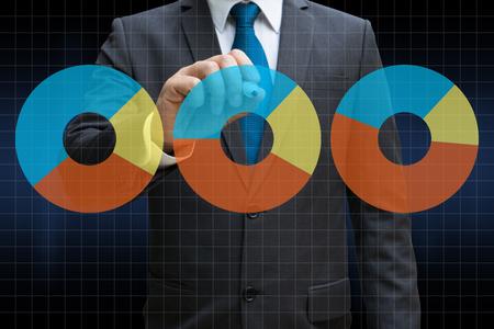 business man drawing the financial pie charts showing growing revenue on touch screen Lizenzfreie Bilder