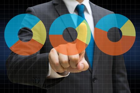 Businessman hand touching the financial pie charts showing growing revenue on touch screen Lizenzfreie Bilder
