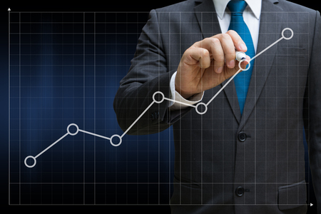 business man drawing the financial line charts showing growing revenue on touch screen