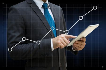 Geschäftsmann, der moderne Tablette mit den Finanzdiagrammen berührt, die wachsenden Einkommen auf Touch Screen zeigen Standard-Bild