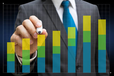 business man drawing the financial bar charts showing growing revenue on touch screen