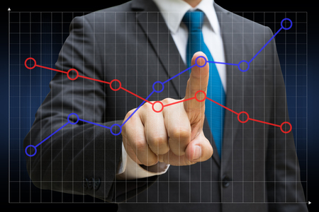 Businessman hand touching the financial line charts showing growing revenue on touch screen