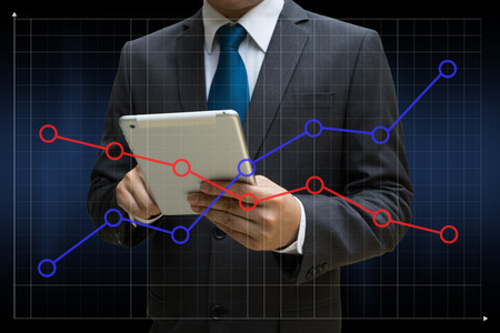 Business Man touching modern tablet with the financial line charts showing growing revenue on touch screen