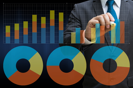 business man drawing the virtual panel of pie chart and other chart , business concept