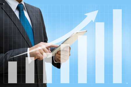 Business Man touching modern tablet with the financial bar charts showing growing revenue on touch screen