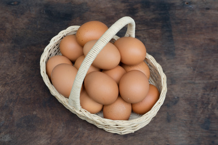 Chicken Egg in a basket on wooden table
