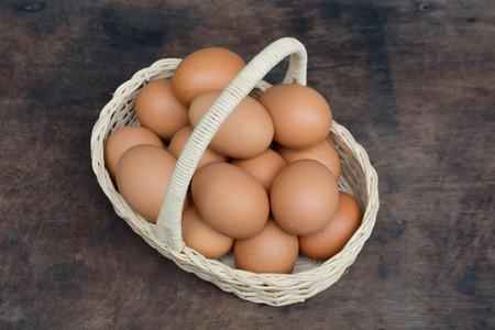 Hühnerei in einem Korb auf Holztisch