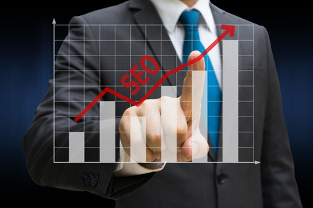Businessman hand touching the SEO bar charts showing growing revenue on touch screen