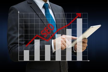 Business Man berührt moderne Tablette mit den SEO-Bar-Charts zeigt wachsende Einnahmen auf Touchscreen Standard-Bild - 81562516