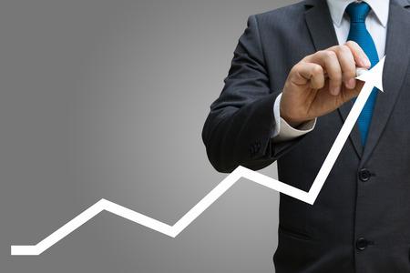 Geschäftsmann Zeichnung der Finanzlinie Charts zeigt wachsende Einnahmen auf Touchscreen Standard-Bild - 82426438