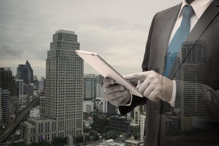 Doppelte Exposition von Geschäftsmann mit Digital Tablet Standard-Bild - 83670935
