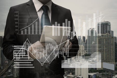 Double exposure of Businessman Using Digital Tablet with the virtual panel of pie chart and other chart , business concept