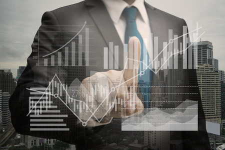 Double exposure of Businessman hand touching the virtual panel of pie chart and other chart , business concept