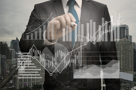 Double exposure of Businessman writing the virtual panel of pie chart and other chart , business concept