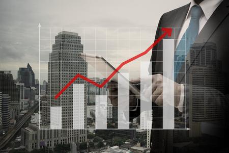 Double exposure of Businessman Using Digital Tablet with the virtual panel of bar chart , business concept Lizenzfreie Bilder