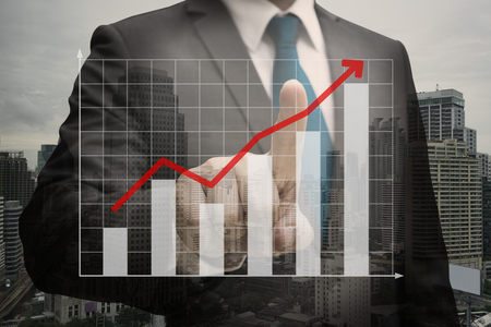 Double exposure of Businessman hand touching the virtual panel of bar chart , business concept