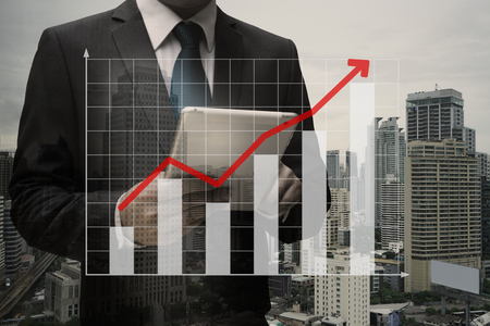 Double exposure of Businessman Using Digital Tablet with the virtual panel of bar chart , business concept Standard-Bild