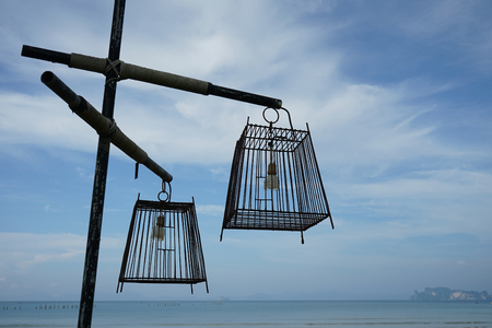 Outdoor lamp made of bird cage on blue sky background