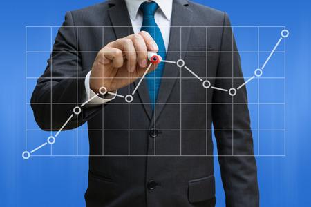 Geschäftsmann, der die Liniendiagramme zeigen wachsenden Ertrag auf Touch Screen zeichnet