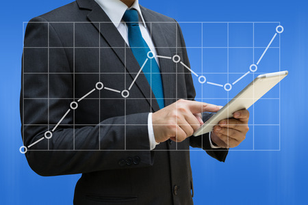 Business Man touching modern tablet with the line charts showing growing revenue on touch screen