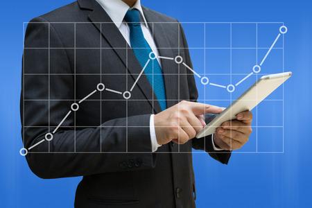 Rührende moderne Tablette des Geschäftsmannes mit den Liniendiagrammen, die wachsendes Einkommen auf Touch Screen zeigen Standard-Bild - 90179730