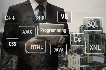 Double exposure businessman hand using digital tablet with virtual panel of programming languages, Computer technology concept