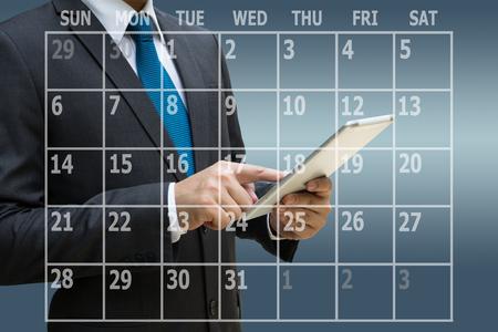 Businessman hand using digital tablet with virtual panel of calendar planner Standard-Bild
