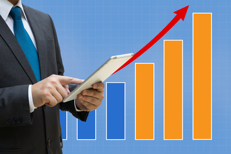 Business Man touching modern tablet with the financial bar charts showing growing revenue on touch screen Standard-Bild - 99224447
