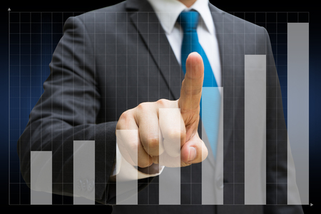 Businessman hand touching the financial bar charts showing growing revenue on touch screen