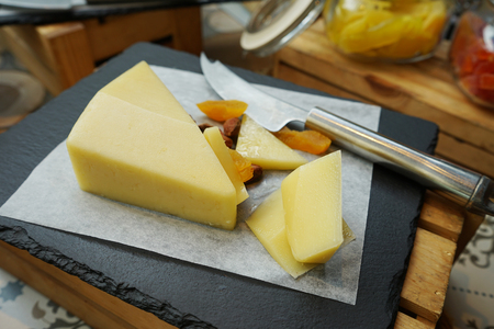 Mature cheddar and knife on chopping board