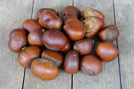 Roasted sweet chestnuts on rustic wooden table.