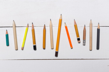 different Short Pencils on white wooden background