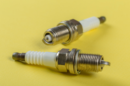 A set of new spark plugs of the car, and spare parts of vehicles on a yellow background.