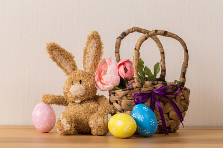 Easter bunny rabbit with  painted egg on wooden background. Easter holiday concept. Imagens