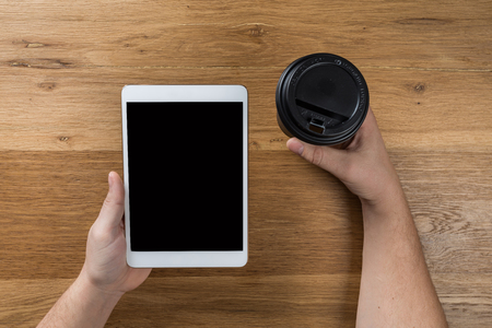 Hand touch on empty screen of tablet above brown table top view, Leave space for display of your content, Technology concept, mock up for montage your content Stock fotó
