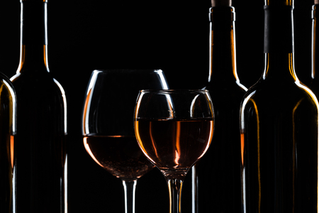 Bar Concept with a Wine Bottle, a Wine Glass and a Cocktail on a Black Background 写真素材