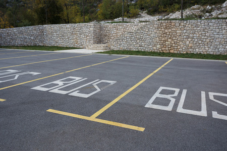 The parking stalls in a parking lot, marked with yellow lines.