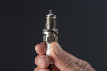 New spark plug in hand on a dark background Reklamní fotografie