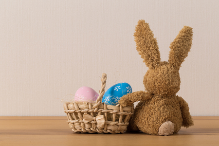 Easter bunny rabbit with  painted egg on wooden background. Easter holiday concept. Stockfoto