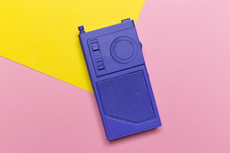 Violet retro radio receiver on a pink yellow pastel background. Top view. Media technology 60s.