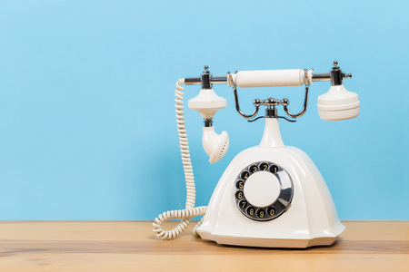 Vintage old white telephone on wooden table with color wall background Imagens