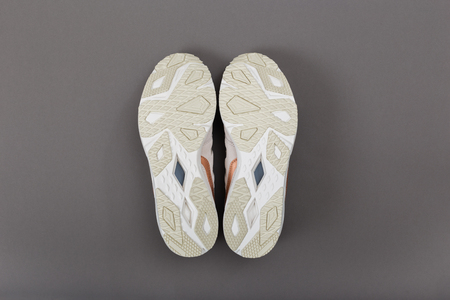Bottom view of a beige sole sports sneaker on a gray background