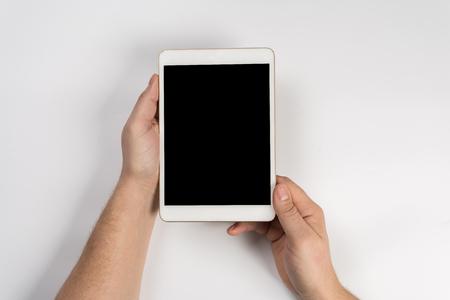 Touchez la main sur l'écran vide de la tablette au-dessus de la vue de dessus de table marron, laissez de l'espace pour l'affichage de votre contenu, concept technologique, maquette pour le montage de votre contenu