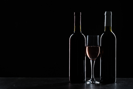 Bar Concept with a Wine Bottle, a Wine Glass and a Cocktail on a Black Background Imagens