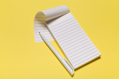 school notebook on a yellow background, notepad on a table.Top view Imagens
